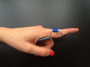 photo avec une main portant une orthese dextension pour traiter le doigt à ressault