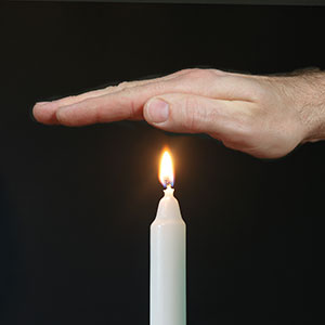 hand burning from candle