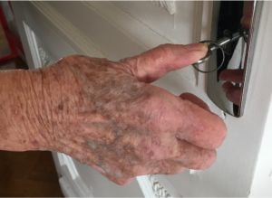 image showing a hand affected by rhizarthrosis who has difficulty opening a door
